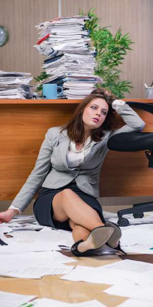 Overworked paralegal surrounded by paperwork